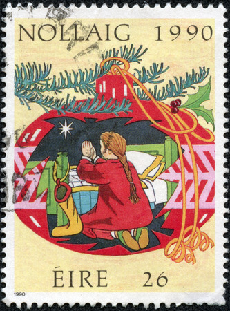 """quo: IRELAND - CIRCA 1990: A stamp printed in Ireland shows Child praying, with the inscription  """"December 1990 """", from the series  """"Christmas & quo t ;, circa 1990 Stock Photo"""