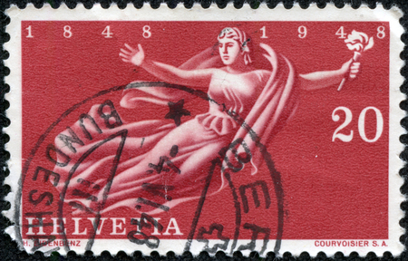 helvetia: SWITZERLAND - CIRCA 1948  A stamp printed in Switzerland, is dedicated to the 100th anniversary of the state, is shown flying Helvetia with a torch, circa 1948 Stock Photo