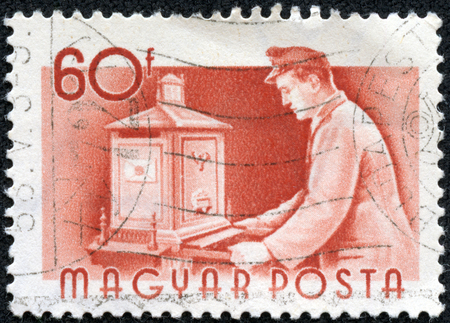 emptying: HUNGARY - CIRCA 1955  a stamp printed in the Hungary shows Postman Emptying Mail Box, circa 1955 Stock Photo