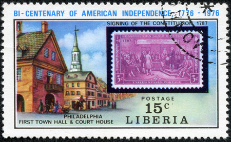 first house: LIBERIA - CIRCA 1976  A stamp printed in Liberia, shows US postage stamp in 1937 signing of the constitution, Philadelphia First Town Hall and Court House, circa 1976
