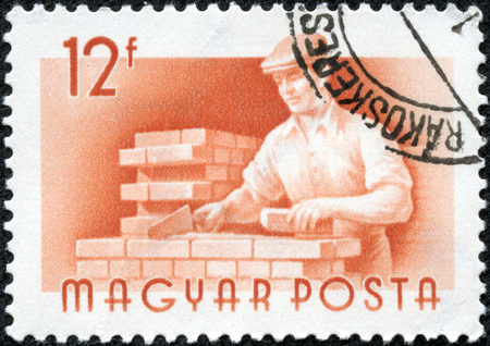 magyar posta: HUNGARY - CIRCA 1959  Orange color stamp printed in Hungary with image of a bricklayer, circa 1959