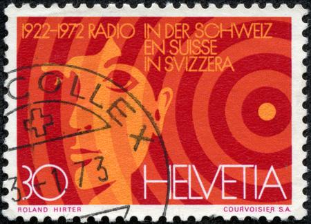 helvetia: SWITZERLAND - CIRCA 1972  A stamp printed in Switzerland, is dedicated to the 50th anniversary of Radio Switzerland, shows the head boy and radio waves, circa 1972 Editorial