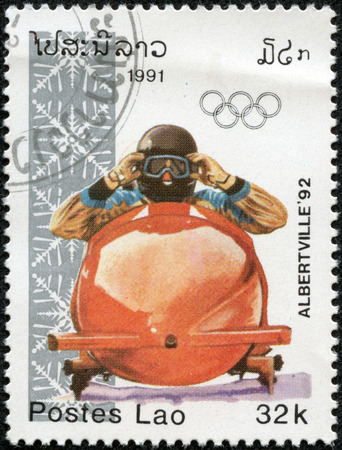 postmail: LAOS - CIRCA 1991  A post stamp printed in Laos shows bobsleigh and devoted the winter Olympic games in Alberville, series, circa 1991 Editorial