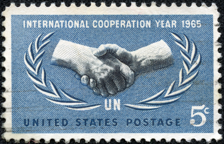 un used: UNITED STATES - CIRCA 1965: A 5 cents stamp printed in the United States shows International Cooperation Year Emblem, circa 1965