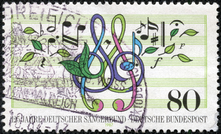 choral: GERMANY - CIRCA 1987: A stamp printed in Germany, is dedicated to the 125th anniversary of German Choral Society, shows musical notes, treble clef, leaves, circa 1987