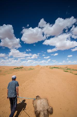 Man pulling a camel in desert