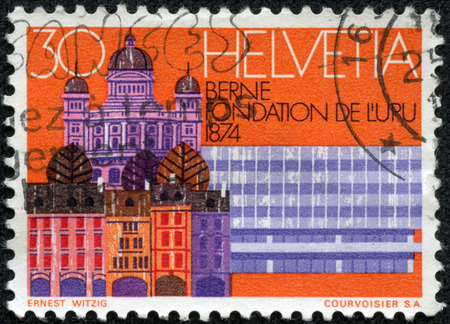 upu: SWITZERLAND - CIRCA 1974  a stamp printed in the Switzerland shows Old Houses, Parliament and RR Station, Bern, Centenary of the UPU, circa 1974 Stock Photo
