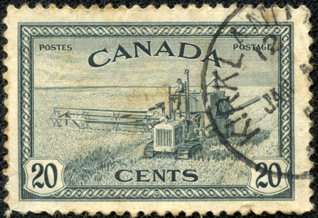 CANADA - CIRCA 1933: A stamp printed in Canada shows wheat harvest and 1930s style combine, circa 1933