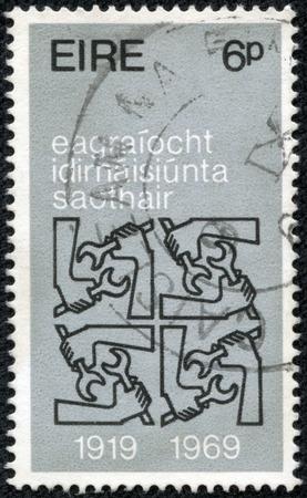 quadruple: IRELAND - CIRCA 1969: A stamp printed in Ireland issued for the 50th anniversary of International Labor Organization shows Quadruple I.L.O. Emblems, circa 1969. Editorial