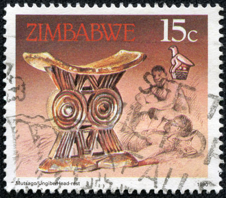 headrest: ZIMBABWE - CIRCA 1990: A stamp printed in Zimbabwe shows image of a Antique gold headrest, series, circa 1990 Stock Photo