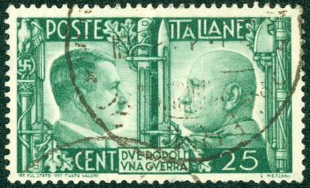 ITALY - CIRCA 1941: A stamp printed by the fascist Italy Post is a portrait of Adolf Hitler and Benito Mussolini It is entitled \ Due popoli una guerra \ (Two nations one war), circa 1941.