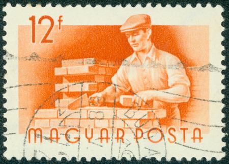 magyar posta: HUNGARY - CIRCA 1959: Orange color stamp printed in Hungary with image of a bricklayer, circa 1959.