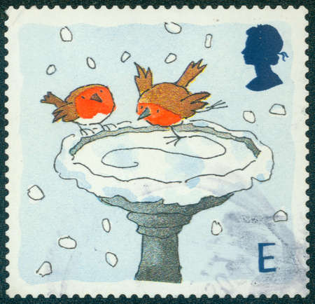 robins: UNITED KINGDOM - CIRCA 2001: A stamp printed in England, is dedicated to Christmas, shows Robins skating on Bird Bath, circa 2001