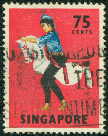 SINGAPORE - CIRCA 1968: Red color postage stamp printed in Singapore with image of a traditional Kuda Kepang dancer on a horse prop.CIRCA 1968 報道画像