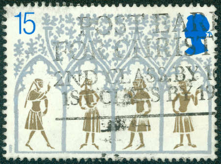 14th century: UNITED KINGDOM - CIRCA 1989: Postage stamp printed in England, is dedicated to 800th Anniversary of Ely Cathedral, shows a 14th Century Peasants from Stained-glass Window, circa 1989