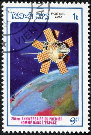 circa: LAOS - CIRCA 1986: A stamp printed in Laos from the 25th anniversary of First Man in Space  issue shows satilite, circa 1986.