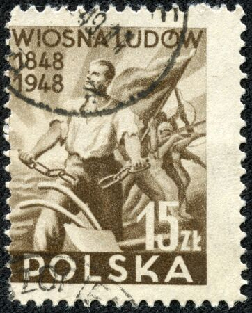 circa: CHONGQING, CHINA - May 9, 2014: A stamp printed in Poland shows foreground a farmer breaks the chain in the background a group of soldiers with arms and a banner in the hands, circa 1948
