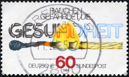bundespost: CHONGQING, CHINA - May 9, 2014:A stamp printed in Germany shows burning match and the inscription Smoke endangers the health, circa 1984