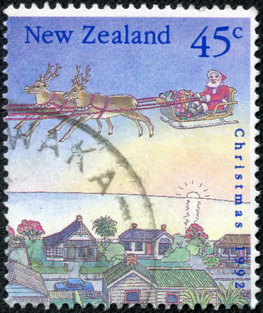 CHONGQING, CHINA - May 10, 2014:A stamp printed in New Zealand dedicated to christmas shows santa with sleigh on the city, circa 1992 Stock Photo