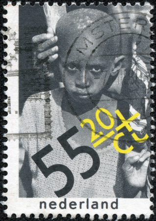 CHONGQING, CHINA - May 10, 2014:A stamp printed in Netherlands dedicated Child Welfare. International Year of the Child. Senegalese boy from Sahel area (The Right to Food), circa 1979