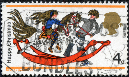christmas military: UNITED KINGDOM - CIRCA 1968: A stamp printed in United Kingdom from the Christmas  issue shows boy and girl with rocking horse , circa 1968. Stock Photo
