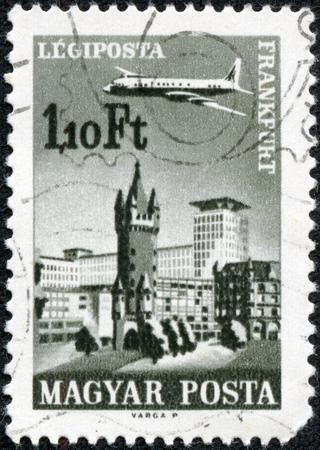 CHONGQING, CHINA - May 10, 2014:A stamp printed in Hungary shows plane abowe Frankfurt am Main, aircraft, Eschenheimer Turm and Eschenheimer Gate, circa 1966