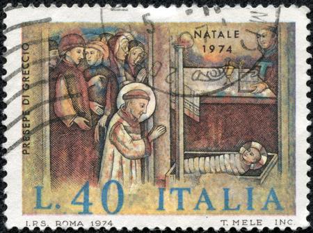 CHONGQING, CHINA - May 10, 2014:a stamp printed by Italy, shows Saint Francis adoring Christ child, circa 1974 Stok Fotoğraf