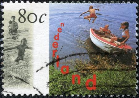 5 月 10 日、中国・重慶 2014:A 切手がオランダで印刷された 1997 シリーズ「水レクリエーション」からの碑文なしボートで遊ぶ子どもたちを示していま
