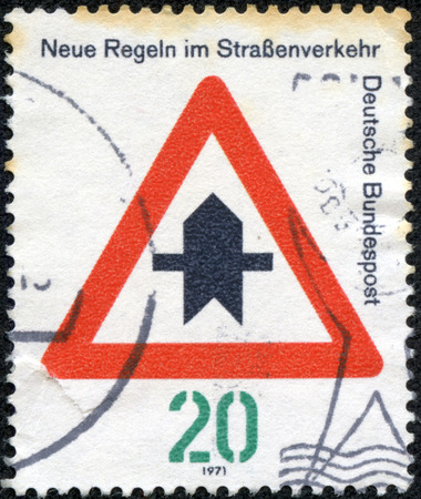 CHONGQING, CHINA - May 10, 2014:A stamp printed in Germany, dedicated to New traffic rules, shows a road sign Proceed with caution, circa 1971