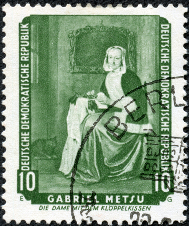 CHONGQING, CHINA - May 11, 2014:A stamp printed in German Democratic Republic (East Germany) shows The Needlewoman (Lacemaker) by Gabriel Metsu, circa 1959