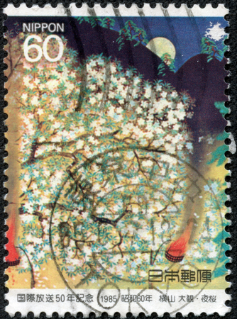 CHONGQING, CHINA - May 11, 2014:A postage stamp printed in Japan shows continuous stamp cherry blossoms at night, series 50th anniversary of radio Japan, circa 1985.