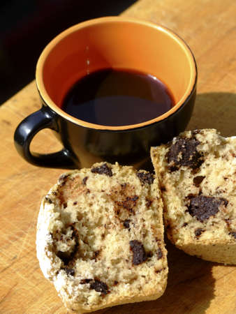 A cup of italian style black coffee and muffin with chocolate chips