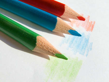 three colored: Three colored pencils on white paper sheet Stock Photo