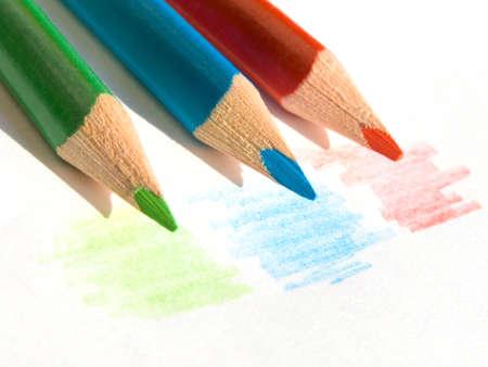 Three colored pencils on white paper sheet 版權商用圖片