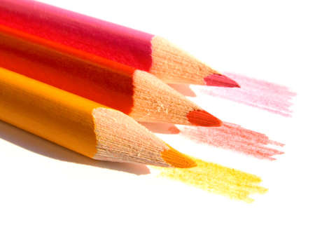 Three colored pencils on white paper sheet Stock Photo