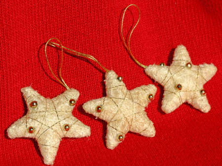 Three Christmas white tissue star decorations on a red background
