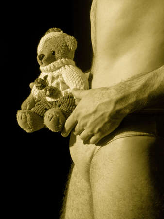 Young man wearing underwear holding a teddybear
