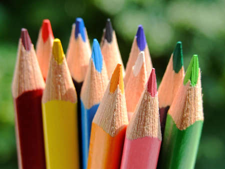 Close-up of some colored pencils over a green background