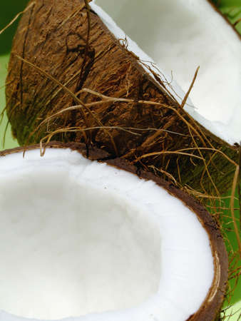 Close-up of an opened coconut fruit over a green background