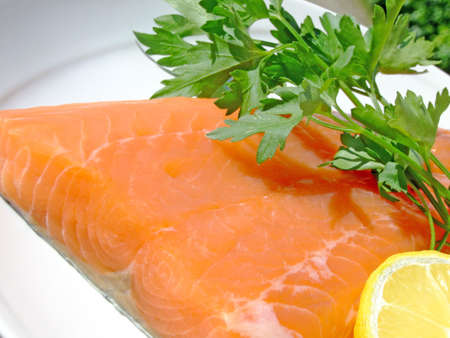 Close-up of a raw salmon fillet with lemon and parsley