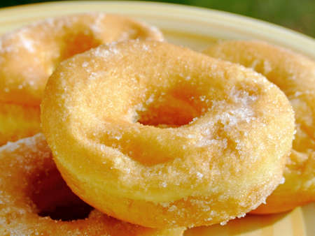 Close-up of some donuts with caster sugar on a dish Stock Photo