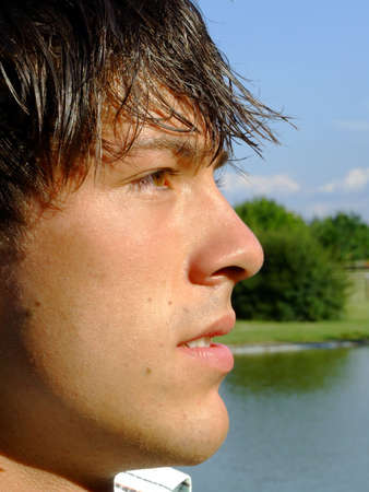 Close-up of a handsome young man at the park in front of a pond