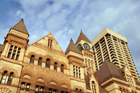 Old city hall of toronto in neo-gothic style near a modern skyscraper under the sunset light Stock Photo