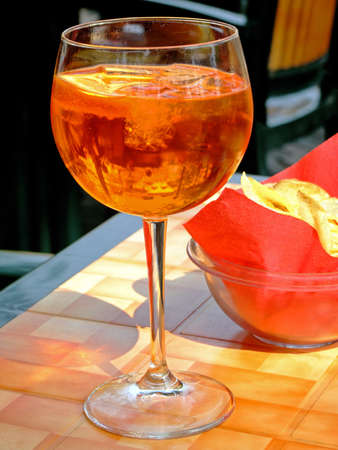 longdrink: Close-up of an orange drink and chips on a cocktail bar table