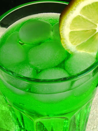 longdrink: Green longdrink with ice cubes and a lemon slice Stock Photo