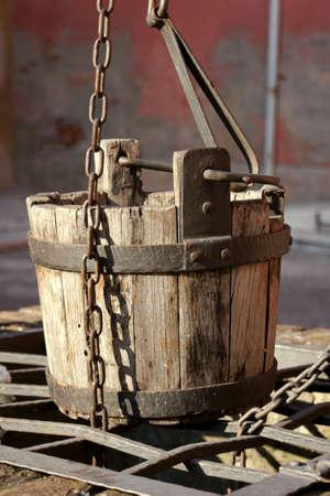 emmer water: Detail van een oude waterput met houten emmer water Stockfoto