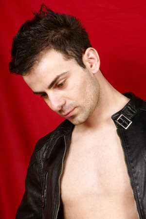 Portrait of a young man with black leather jacket over a red background photo