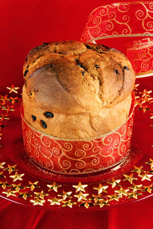 A freshly baked Panettone, the italian Christmas fruit cake with red and golden ribbon served on a red glass plate over a red background. photo