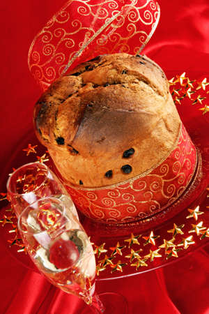 Panettone the italian Christmas fruit cake with red and golden ribbon served on a red glass plate over a red background. Two glasses of champagne in the foreground. Selective focus.