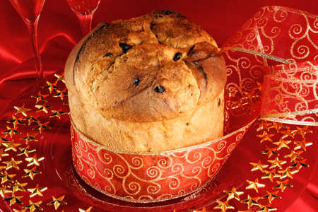 A freshly baked Panettone, the italian Christmas fruit cake with red and golden ribbon served on a red glass plate over a red background.